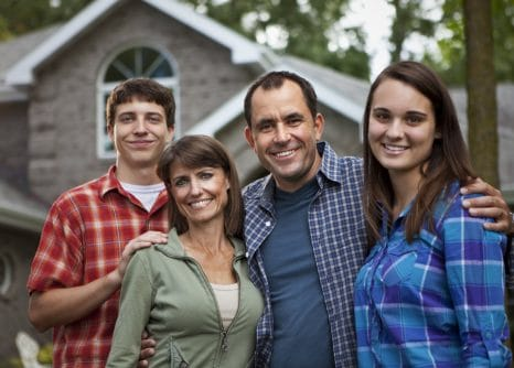 Family in front of suburban home